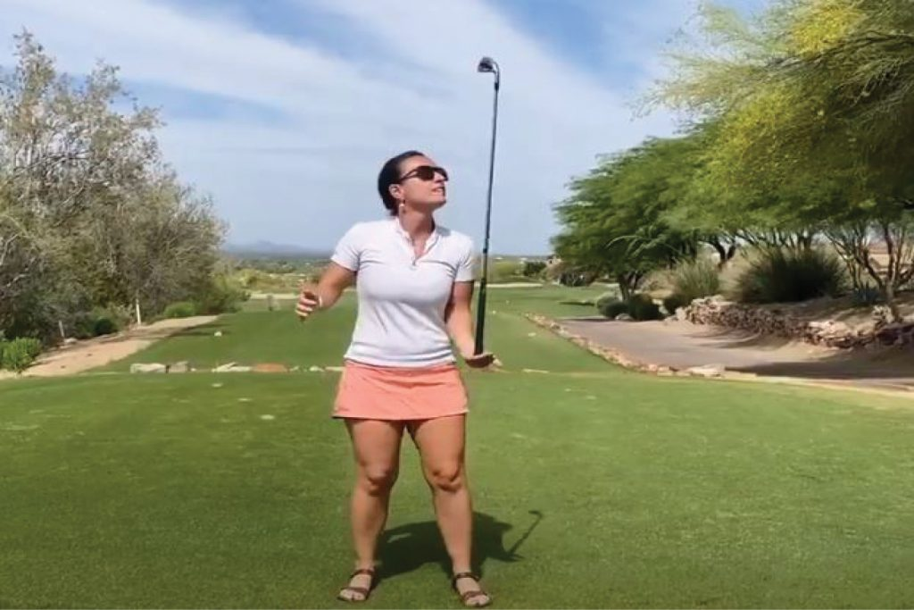 golfer balancing a club on hand